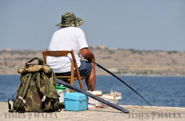 A man tries to catch fish in Bugibba on July 13. Photo: Chris Sant Fournier