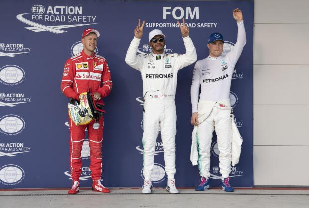 Ferrari driver Sebastian Vettel (left) of Germany and Mercedes driver Lewis Hamilton (center) of Great Britain and Mercedes driver Valtteri Bottas (right) of Finland wave to the crowd.