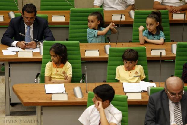 Two schoolgirls are evidently amused as Sports Parliamentary Secretary Chris Agius (left) concentrates on his mobile phone during their annual parliamentary session of EkoSkola, held in Parliament House in Valletta on May 27. The activity gives students the opportunity to meet MPs and discuss their environmental concerns. Photo: Darrin Zammit Lupi