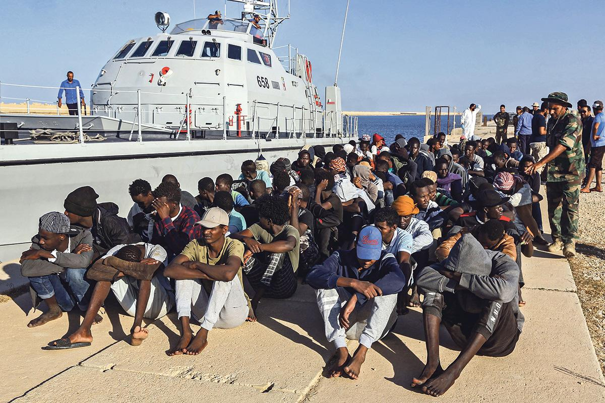 This picture taken on October 1 shows rescued migrants sitting on a pier next to a Libyan coast guardship in the town of Khoms, 120 kilometres east of the capital.