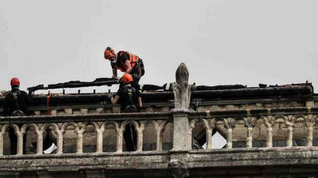 Workers seen on the roof of Notre Dame Cathedral.