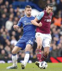 West Ham's Andy Carroll is closely marked by Gary Cahill.