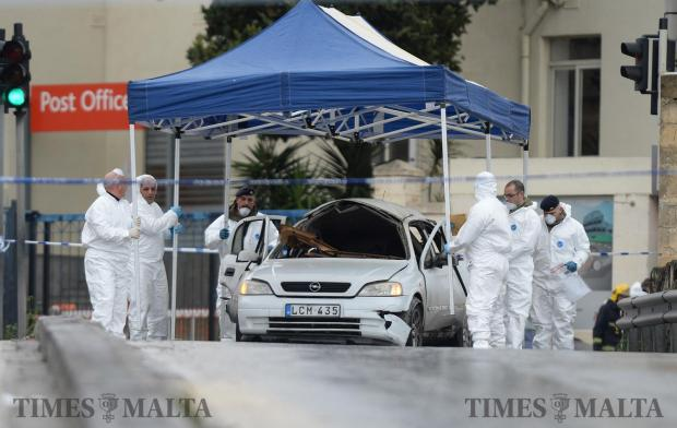 Police officers erect a tent over the car which exploded after a car bomb went off killing 65 Victor Calleja, of Ħamrun. The incident happened in Qormi just outside Maltapost offices on January 29. Photo: Matthew Mirabelli