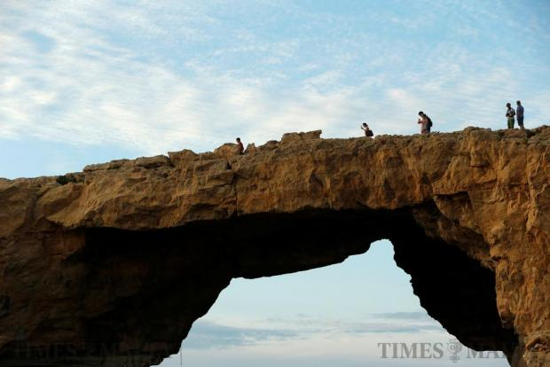 Tourists walk on the Azure Window, a 50 metre high rock arch, at Dwejra Point cliffs on the island of Gozo on September 23. Believed to have been formed millions of years ago, the arch is in danger of collapse due to natural erosion. Photo: Darrin Zammit Lupi