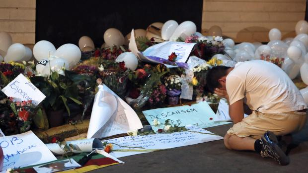 A man kneels as he mourns in front of flowers placed in tribute to the victims of the Kiss nightclub fire in Brasil.