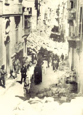 King George VI walking through the streets of Senglea, here at Two Gates Street, towards Victory Street, accompanied by Canon Emmanuel Brincat.