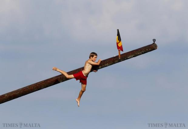 "A child slips off the ""gostra"", a pole covered in grease, during the celebrations for the religious feast of St Julian, patron of the town of St Julian's on August 30. In the traditional ""gostra"", a game believed to stretch back to the Middle Ages, young men, women and children have to make their way to the top of a pole and try to uproot one of the flags to win prizes. Photo: Darrin Zammit Lupi"
