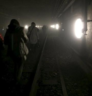 Passengers walk on underground metro tracks to be evacuated after an explosion at Maelbeek train station.