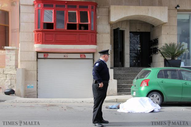 A Police officer stands by the corpse of German tourist Rainer Mader shortly after he was hit by a car and pinned against a parked pick-up truck on January 12 in Sliema. Photo: Paul Spiteri Lucas