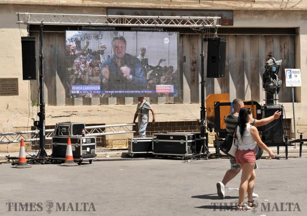 The last of the PN supporters who gathered to await the result of the general election in front of the PN headquarters walk away in disappointment while a jubilant Konrad Mizzi looks down through a big screen from the Counting Hall, moments after the result was announced on June 4. Photo: Chris Sant Fournier