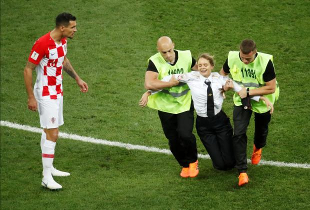 Croatia's Dejan Lovren looks on as one of the invaders is dragged off the pitch. Photo: Reuters