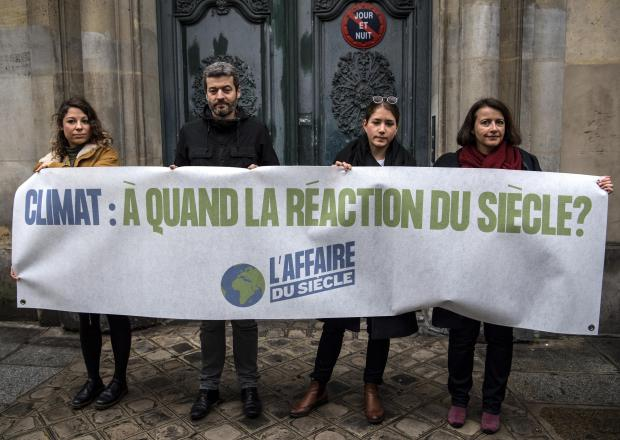 NGO representatives hold a banner as they stage a protest in front of the administrative tribunal in Paris.