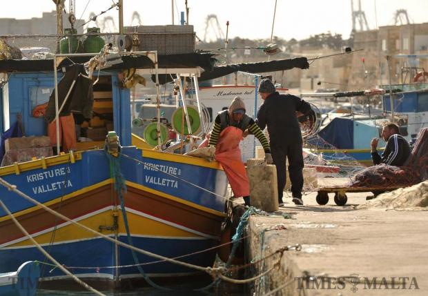 A fishing crew and their Luzzu at Marsaxlokk harbour on January 4. Photo: Chris Sant Fournier