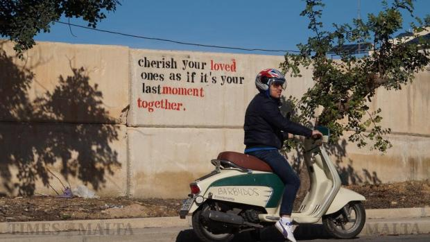 A biker goes past a poignant message first written on Facebook by the boyfriend of motorcyclist Johanna Boni, who died instantly in a horrific crash on the same spot in Naxxar a few days earlier, on January 10. Some 300 motorcyclists gathered there to honour her memory. Photo: Steve Zammit Lupi