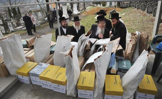 Rabbis from England and US look in the town of Iasi, 410 kilometres north of Bucharest, at boxes and bags containing the remains of some 40 Jews killed during the Holocaust. Photo: Daniel Mihailescu