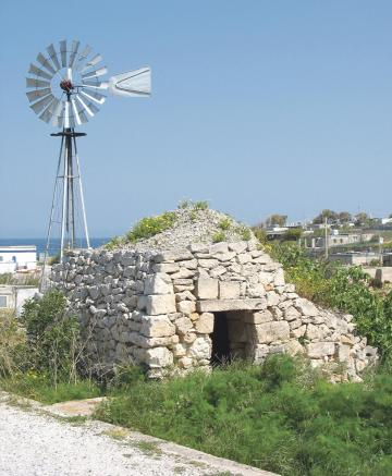 A square girna with small stones on its roof near a windmill.