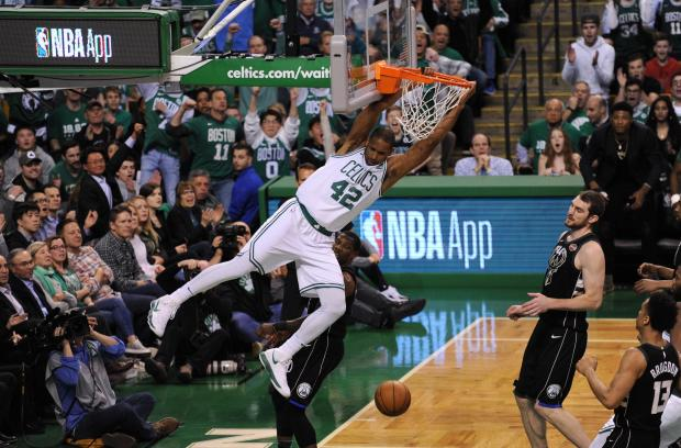 Boston Celtics forward Al Horford (42) hangs onto the rim after dunking the ball during the first half in game two of the first round of the 2018 NBA Playoffs against the Milwaukee Bucks at TD Garden. Photo Credit: Bob DeChiara-USA TODAY Sports