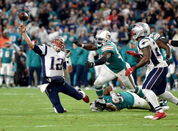 142c46669b4 New England Patriots quarterback Tom Brady (12) throws under pressured from  Miami Dolphins outside