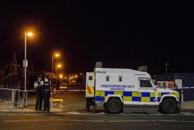 Police at the scene of an explosive device attack on the west Belfast home of Sinn Fein figure Bobby Storey.