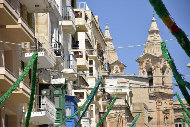 A resident steps out onto her balcony in Cathedral Street in Sliema on August 24. Photo: Mark Zammit Cordina