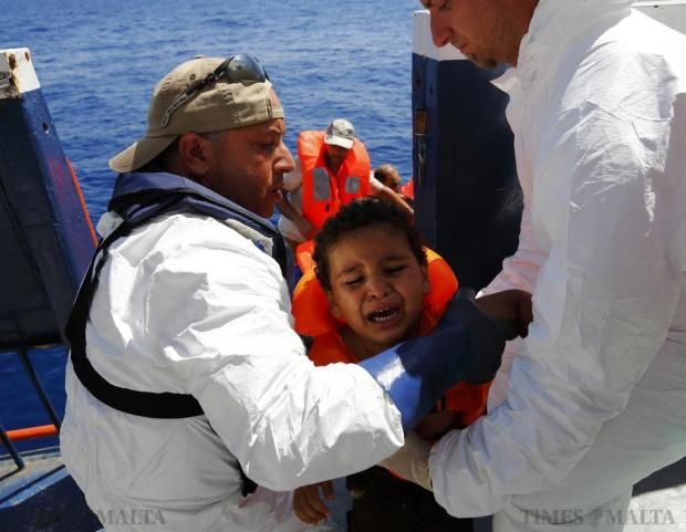 A migrant child is brought onto the Migrant Offshore Aid Station (MOAS) ship MV Phoenix after being rescued from an overloaded wooden boat 10.5 miles (16 kilometres) off the coast of Libya on August 6. An estimated 600 migrants on the boat were rescued by the international non-governmental organisations Medecins san Frontiere (MSF) and MOAS without loss of life on Thursday afternoon, a day after more than 200 migrants are feared to have drowned in the latest Mediterranean boat tragedy after rescuers saved over 370 people from a capsized boat thought to be carrying 600. Photo: Darrin Zammit Lupi