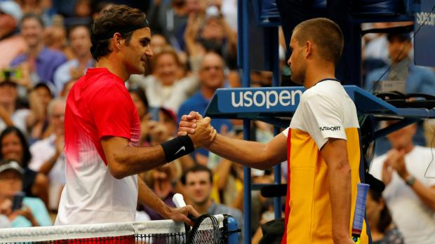 Roger Federer of Switzerland (L) celebrates winning his second round match against Mikhail Youzhny of Russia (R).