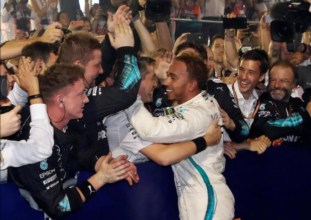 Mercedes' Lewis Hamilton celebrates with his team after winning the race.