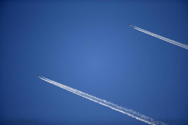 A Qatar Airways Boeing 787-8 Dreamliner (left) flying from Casablanca to Doha, and an Air Algerie Airbus A330-202 (right) enroute to Dubai from Algiers, leave contrails in the the sky as they fly over Malta on October 4. Photo: Darrin Zammit Lupi