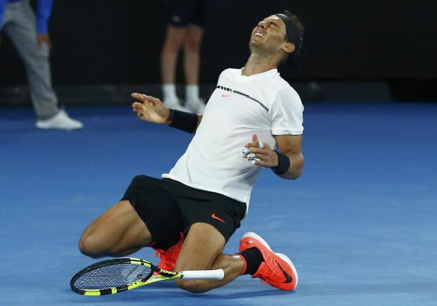 Spain's Rafael Nadal falls onto the court as he celebrates winning his men's singles semi-final match.