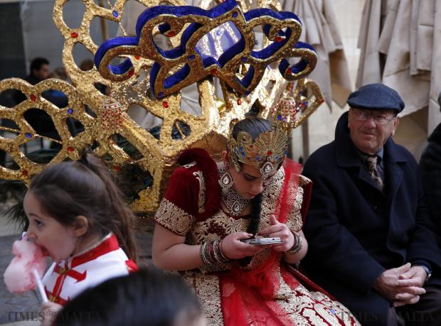 A carnival dancer uses her phone while sitting next to onlookers on a bench during carnival festivities in Valletta on February 7. Photo: Darrin Zammit Lupi