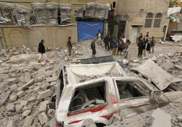 Houthi militants and people gathering at the site of a Saudi-led air strike in Yemen's capital Sanaa yesterday.