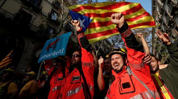 Firemen should slogans under a Catalan flag in Barcelona. Photo: Reuters