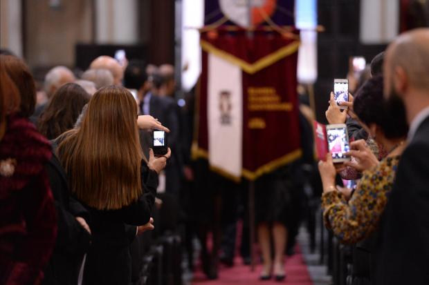 Family and friends take photographs with their mobile phones as graduates enter the University Church in Valletta on December 5. Photo: Matthew Mirabelli