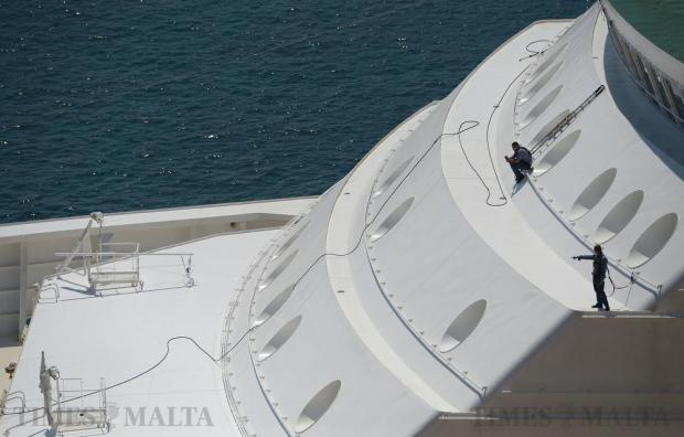 Two workers stand on a small deck of a cruise liner in the Grand Harbour on August 14. Photo: Matthew Mirabelli