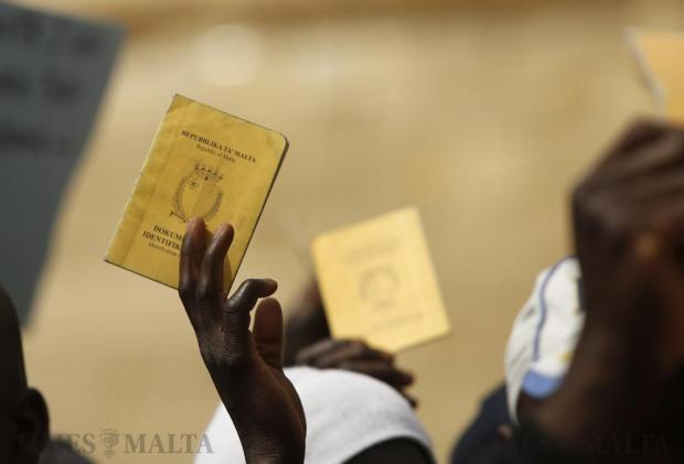 African immigrants hold up their identity documents during a demonstration to call for a change in the system regulating migrant workers, more integration and protection of their basic human rights in Valletta on March 16. Photo: Darrin Zammit Lupi