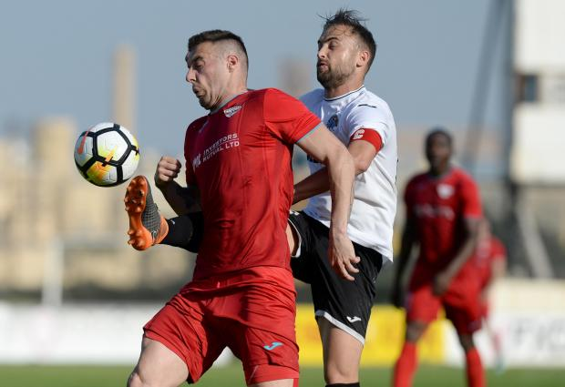 Balzan's Bojan Kaljevic (left) and Hibernian's Andrei Agius fight for the ball during their Premier League match at the Hibernian's Stadium in Paola on April 21. Photo: Matthew Mirabelli