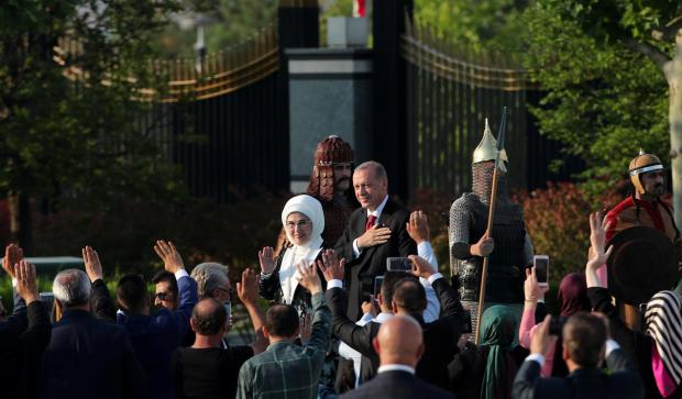 Turkish President Tayyip Erdogan, accompanied by his wife Emine Erdogan, arrives for a ceremony at the Presidential Palace in Ankara, Turkey.