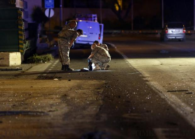 Armed Forces of Malta explosive ordnance disposal experts look for clues on the scene of a bomb attack on a vehicle which left three people seriously injured on a busy road in Marsa on September 26. Photo: Darrin Zammit Lupi