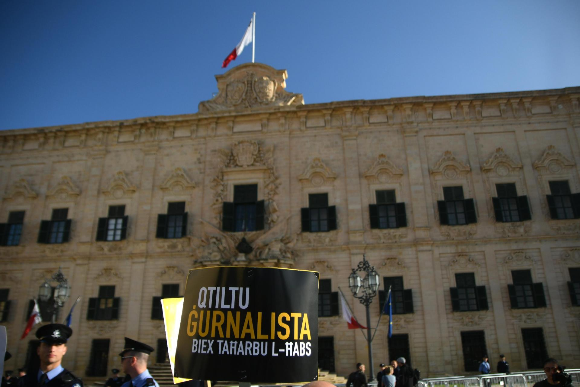 Police keep watch as protesters hold up placards outside Castille. Photo: Jonathan Borg