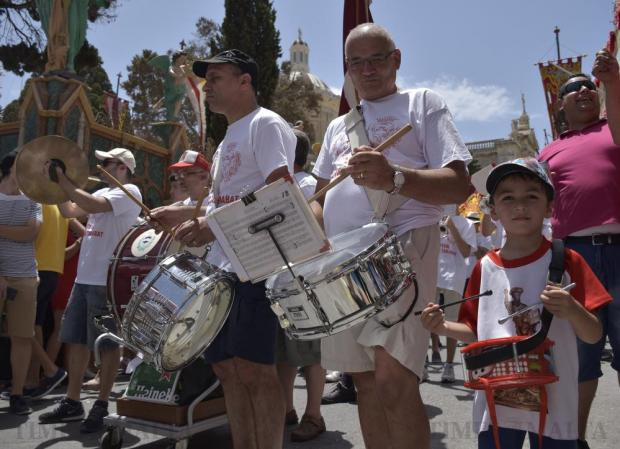 A young boy plays the drums next to a band member during the feast of St Paul in Rabat on July 3. Photo: Mark Zammit Cordina