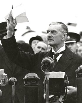 "Chamberlain pictured on his return to the UK from the Munich summit, declaring that the piece of paper he was holding in his hand was an agreement that meant ""peace for our time""."