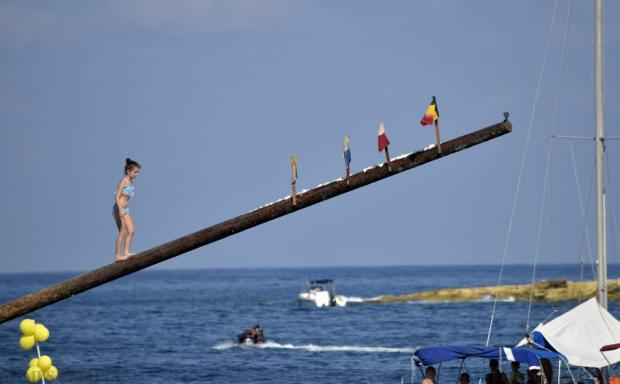 A young girl attempts to run up the greasy pole (gostra) in St Julian's on 30 August. Photo: Mark Zammit Cordina