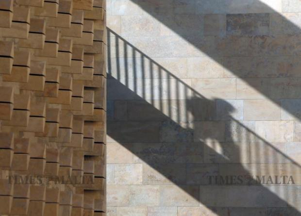 A member of parliament casts a shadow as he walks across a bridge connecting the two blocks of the Parliament House in Valletta on May 30. Photo: Darrin Zammit Lupi