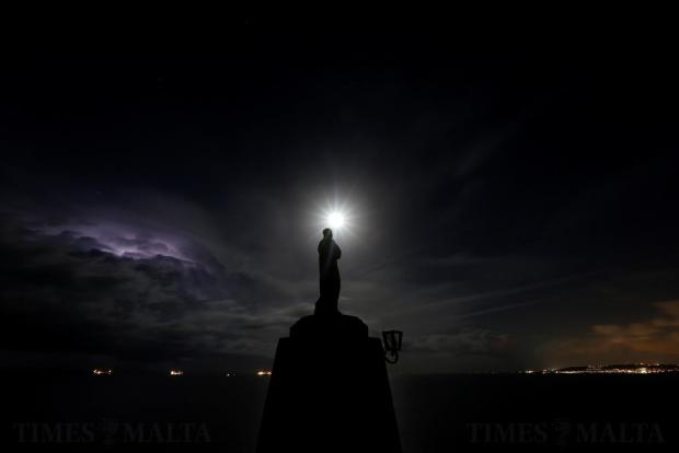A statue of the Madonna overlooks the sea as the supermoon rises and a lightning storm strikes off the coast at l-Ahrax tal-Mellieha on November 14. Photo: Darrin Zammit Lupi