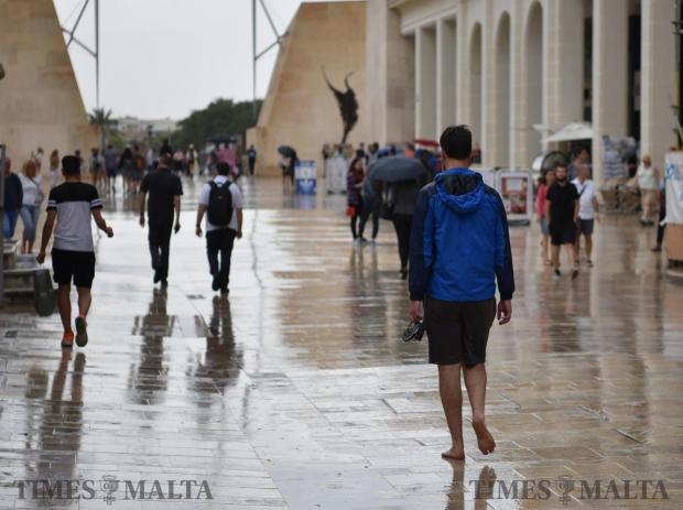 A man walks up Republic Street Valletta bare foot holding his flip-flops during a downpour on June 06. Photo: Mark Zammit Cordina