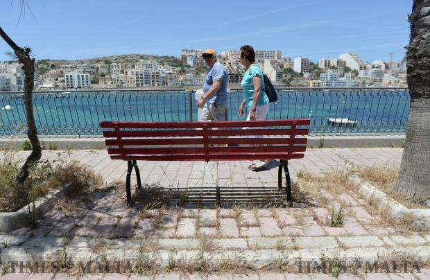 A couple walk along the promenade in St Paul's Bay on May 14, which is covered in overgrown grass. Photo: Matthew Mirabelli