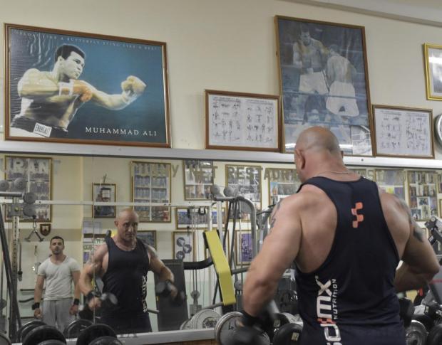A man at Bertu's Gym in Għargħur lifts weights in front of a poster of Muhammad Ali on June 6. Photo: Mark Zammit Cordina