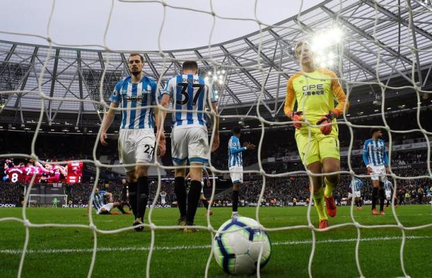 Huddersfield Town's Jonas Lossl looks dejected after West Ham's fourth goal.