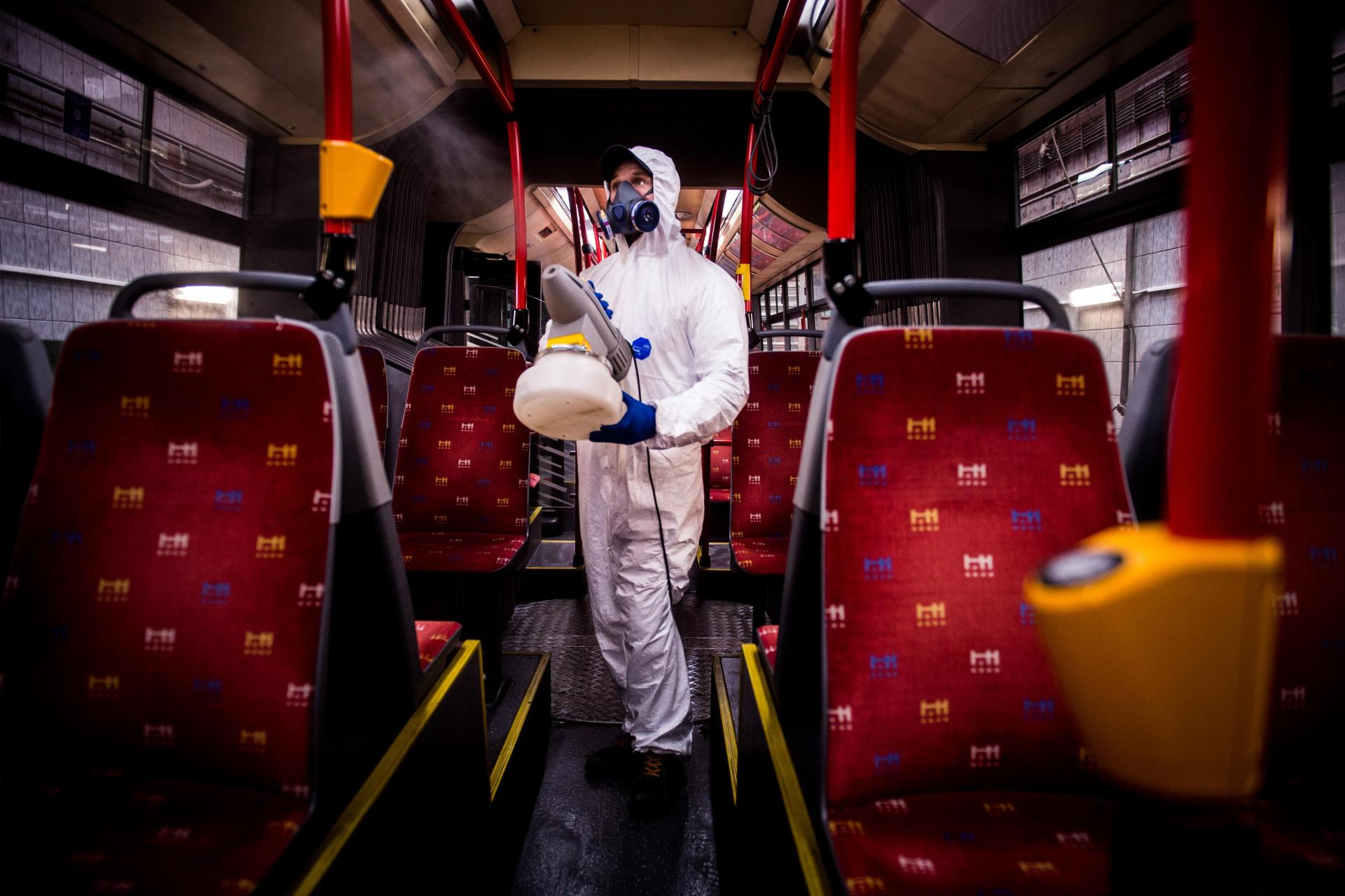 A worker wearing protective clothes disinfects an interior of a public bus in a bus-wash station in Bratislava, Slovakia. Photo: AFP