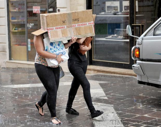 A couple of women use a cardboard box to shelter under during an unseasonal downpour on June 24. Photo: Chris Sant Fournier